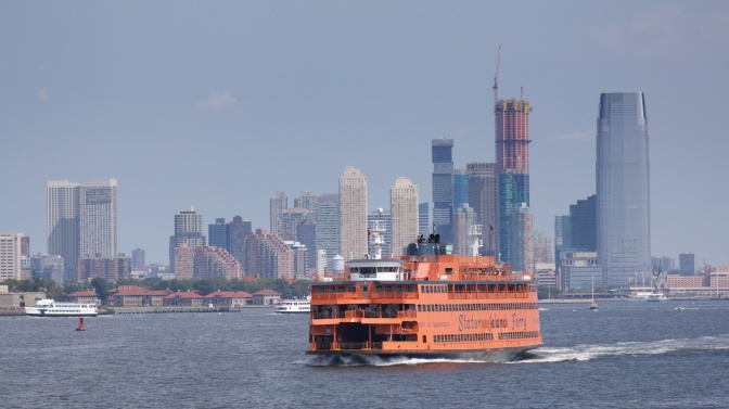 Staten Island Ferry in water. Jersey City skyline in the background.