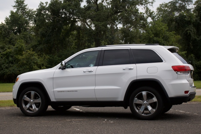 2014 Jeep Grand Cherokee, white, parked in a parking lot. Trees are in the background.