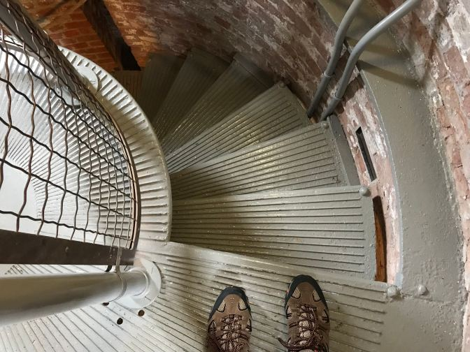 View of lighthouse stairs facing down. A man's shoes are in the foreground.