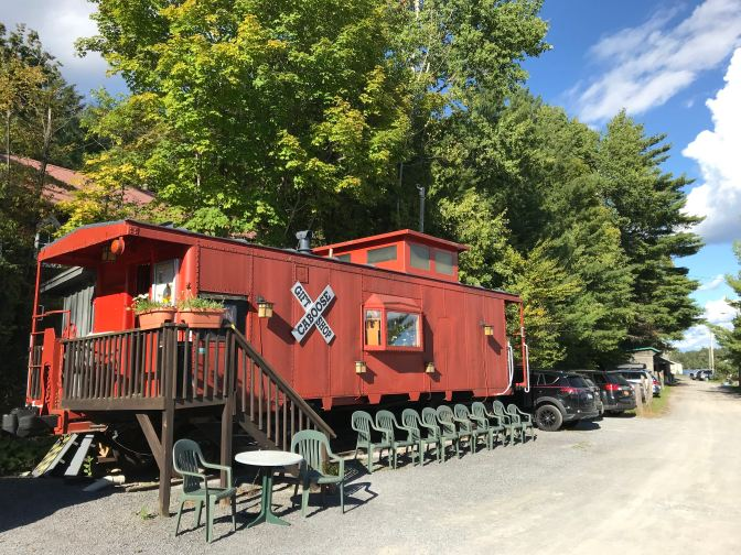 Red Caboose gift shop, with plastic chairs lined up in front of it.