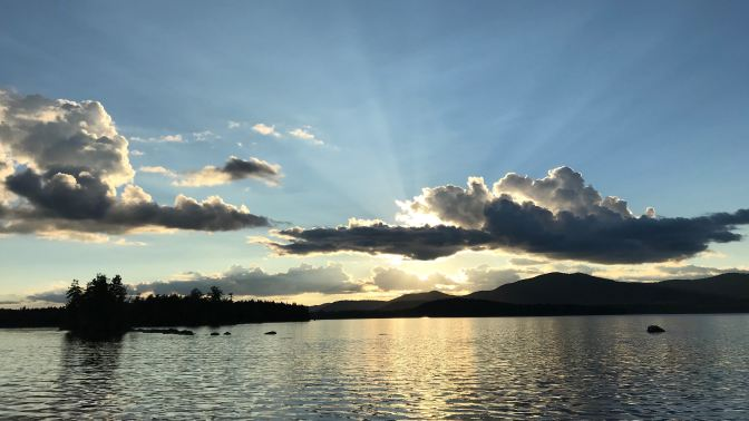 Sunset on Raquette Lake. Trees and mountains are in the distance.