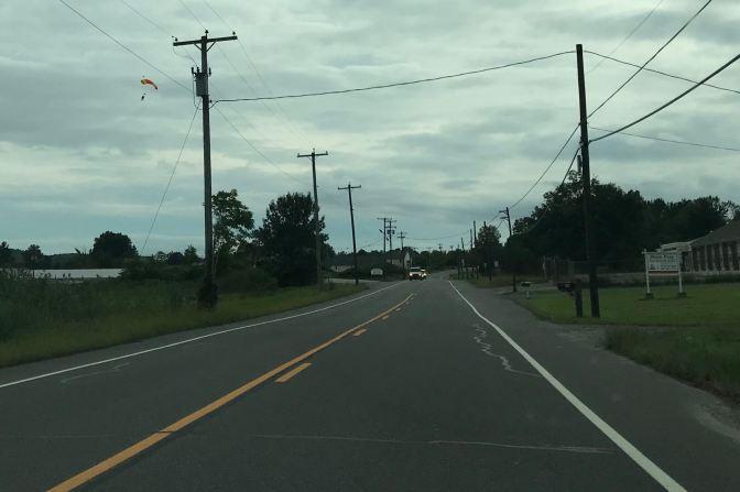 Sky diver floating over road.