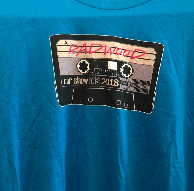 Blue t-shirt with image of cassette tape on front, with Radwood car show 2018 written on the tape.