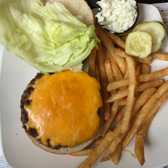 Cheeseburger, pickles, french fries, and coleslaw.