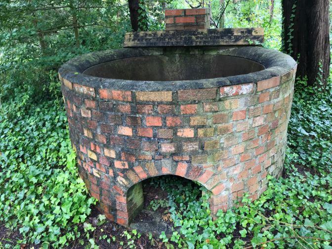Brick tar pot in backyard of museum.
