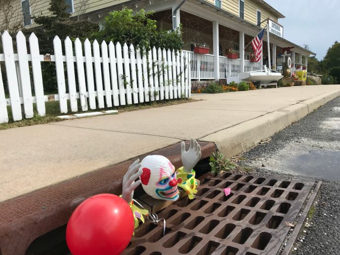 Clown's head, hands, and red balloon coming out of storm drain.