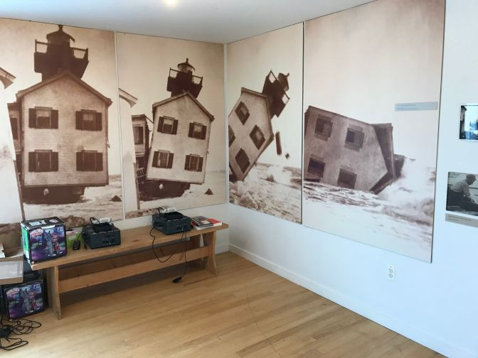 Four wall-size photographs showing Tucker Island Lighthouse falling into the ocean.