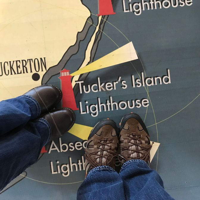 Floor map of NJ lighthouses. Two people's feet are in the photo near Tucker's Island Lighthouse.