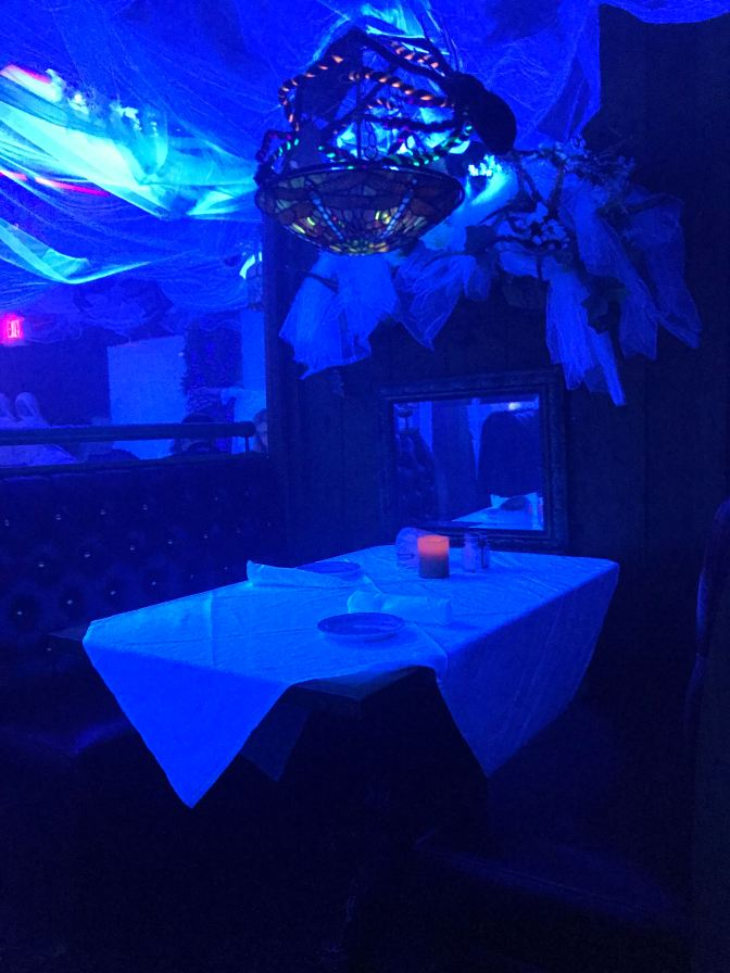 Room, illuminated in black light, decorated for Halloween.