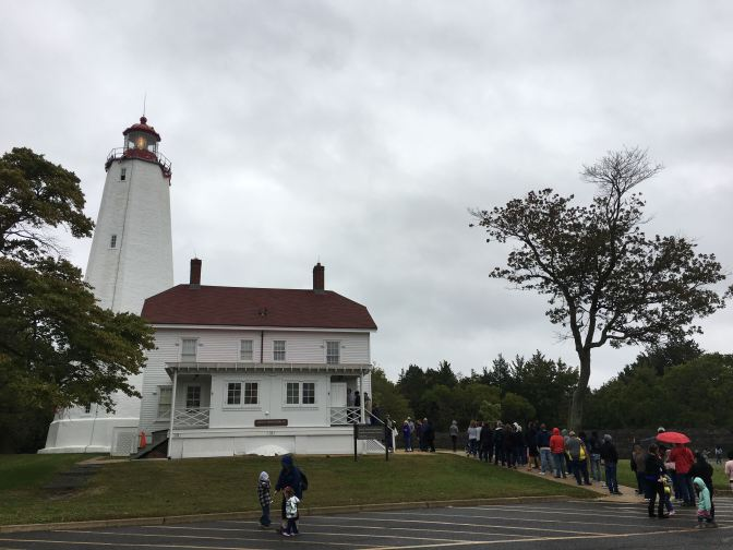 Exterior of Sandy Hook Lighthouse, with a line of people extending out to the parking lot from the rear porch.