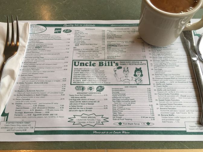 Menu placemat for Uncle Bill's Pancake House, along with a cup of coffee and silverware.