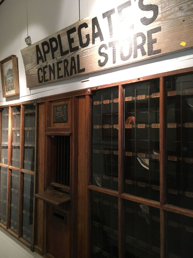 Facade of post office. A sign that says APPLEGATE'S GENERAL STORE is hung on the wall above it.