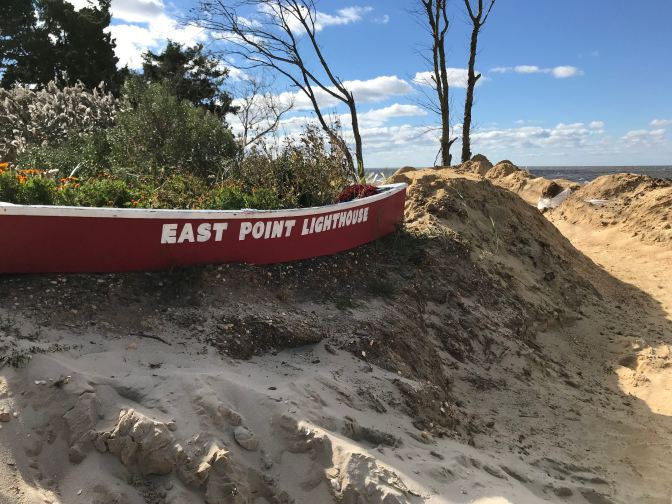 Sign on beach that says East Point Lighthouse.