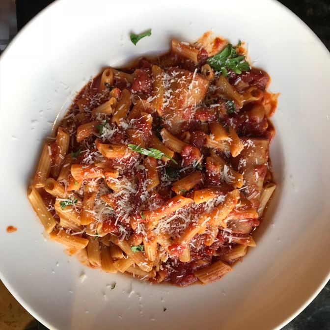 Sausage and pasta with red sauce, on a white plate.