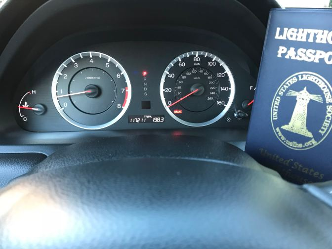 Car dashboard with odometer that reads 117211 miles. Lighthouse Passport book is on the right side of the picture.