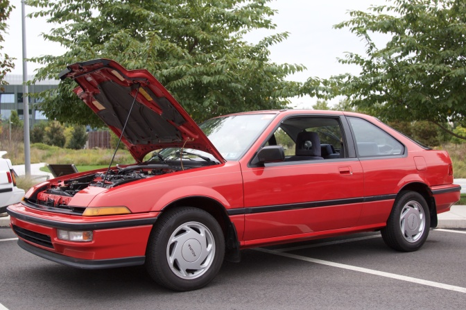Red Acura Integra with its hood up.