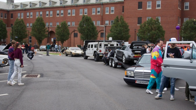 View of cars, with spectators dressed in 1980s and 1990s attire.