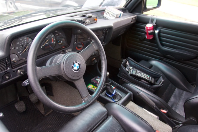 Interior of BMW 325i with old cell phone, radar detector, and cassette tapes.
