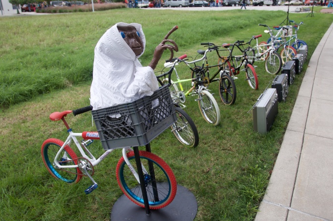 Model of E.T. in a bicycle basket, in front of a row of children's bikes from the 80's and boombox stereos.