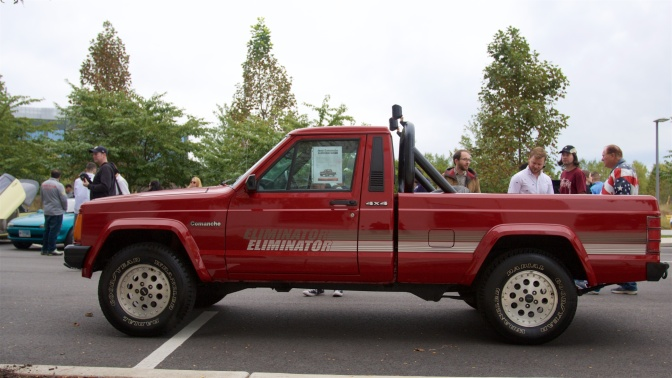 Red Jeep Comanche Eliminiator pickup truck. Spectators mill around it.