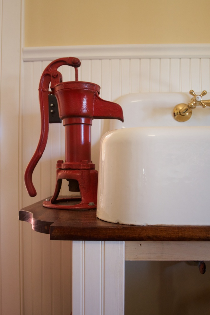 Red water pump and sink in kitchen.
