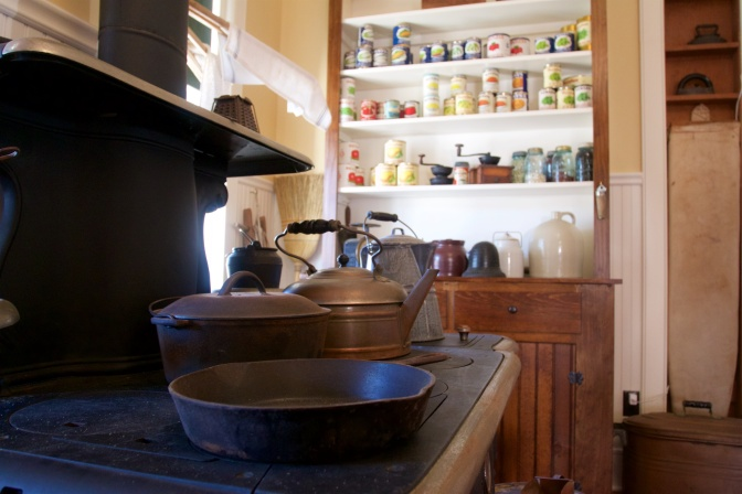 Pots and pans on stove, with cabinet with canned goods in background.