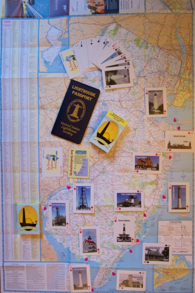 Map of New Jersey with cards arranged at the relevant lighthouses and a Lighthouse Passport book on it as well.
