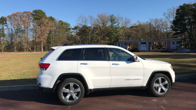 2014 white Jeep Grand Cherokee, parked in circular lot in front of main gate to WheatonArts.