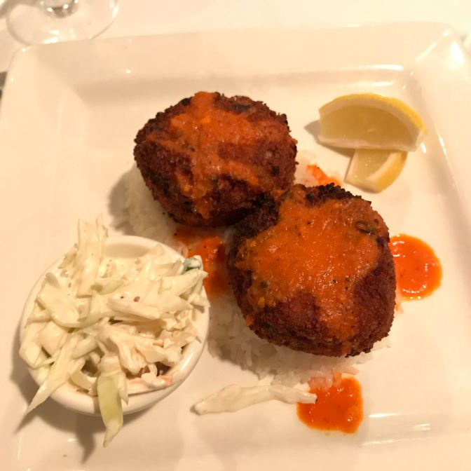 Crab cakes on plate with lemon slices and slaw.