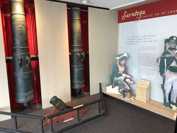 Two British cannons, recessed into the wall, alongside a display of the battle.