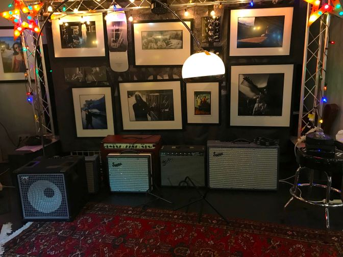 Stage with guitar amplifiers. Photographs hang from the wall behind the stage.
