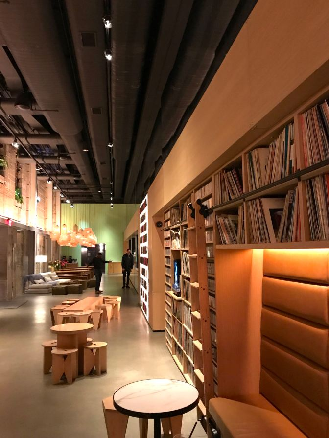 Hotel lobby. Small wooden chairs and tables are in the middle of the floor. Two men are in the background. Shelves filled with LP records and cassettes line the walls.
