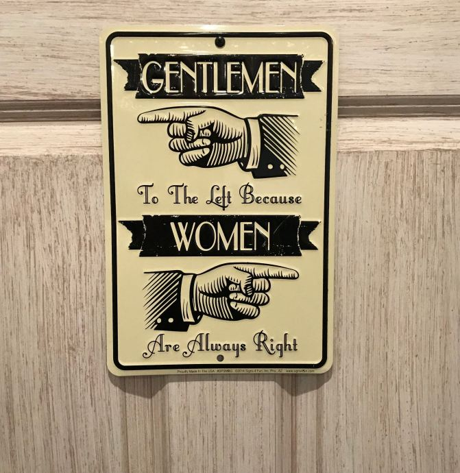 Sign that says GENTLEMEN TO THE LEFT BECAUSE WOMEN ARE ALWAYS RIGHT (hands point left and right).