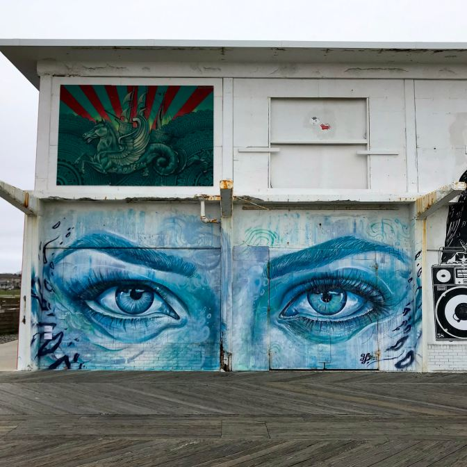Mural of unicorn in front of sailing ship and another of face focused on two large eyes.