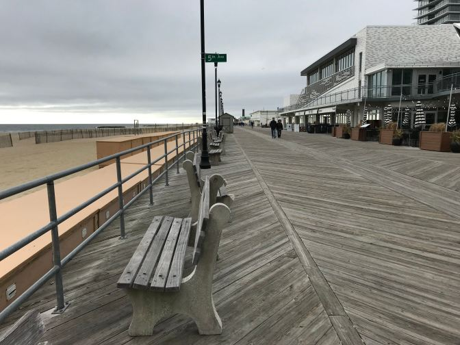 Bench along the Asbury Park Boardwalk. A sign for 5th Avenue is in the background on a pole.