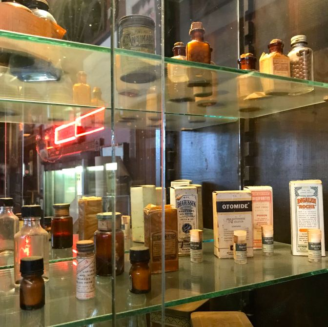 Glass shelves with old medicines and ointments from 100 years ago.