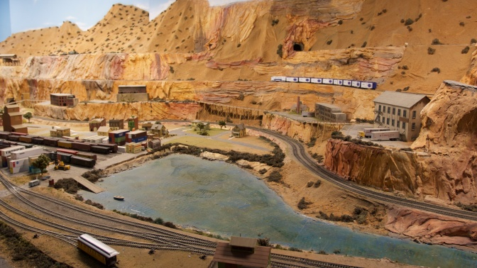Desert canyon train set, with train yard and river in foreground.