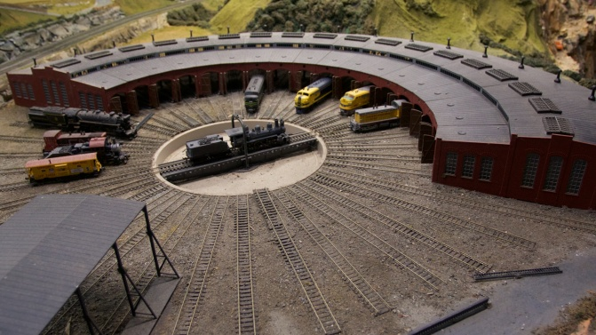 Roundhouse train yard with nine trains in the roundhouse.