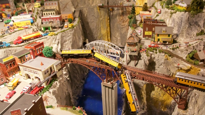 Diorama of town with railroad bridge across canyon, and a derailed train hanging off the bridge.