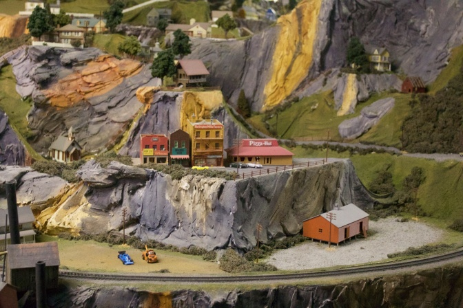 Mountain village scene, with a pizza hut model on the top of the hill, and several small cars around it.