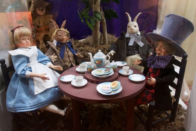 Alice in Wonderland doll exhibit with Alice and several other characters having a tea party.