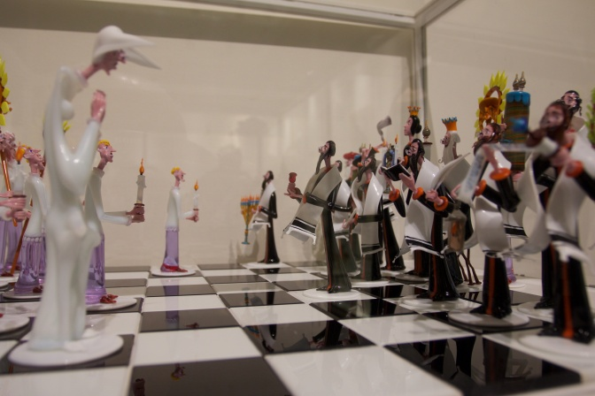 Chess set. The pieces are made of glass, and are figures dressed as Catholic clergy and Jewish religious leaders.