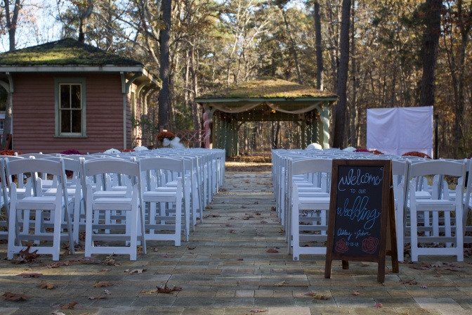 Outdoor wedding setup, with white chairs in rows before a small gazebo. A sign says WELCOME TO OUR WEDDING.