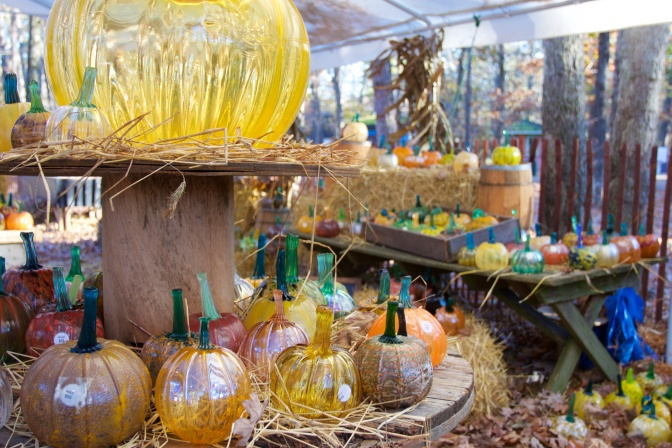Pumpkin patch under large white tent. The pumpkins are all glass.