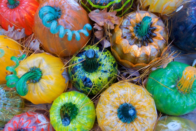 Birds-eye view of glass pumpkins, in multiple colors including yellow, orange, red, and green.
