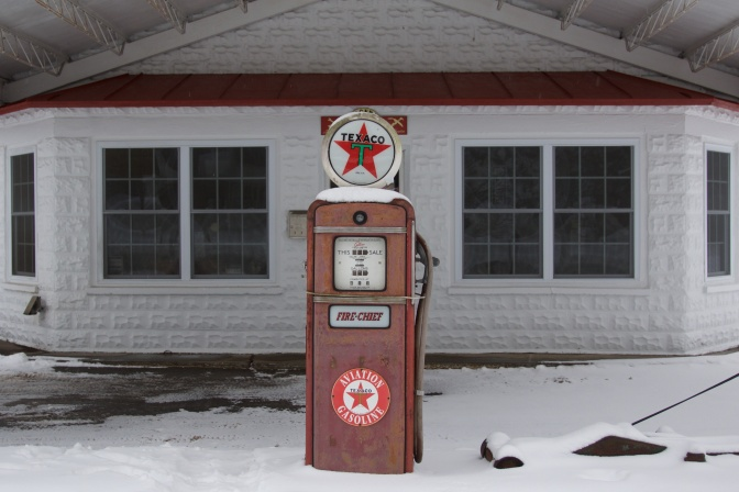 Old gas station, with a single red pump in the middle of the frame.