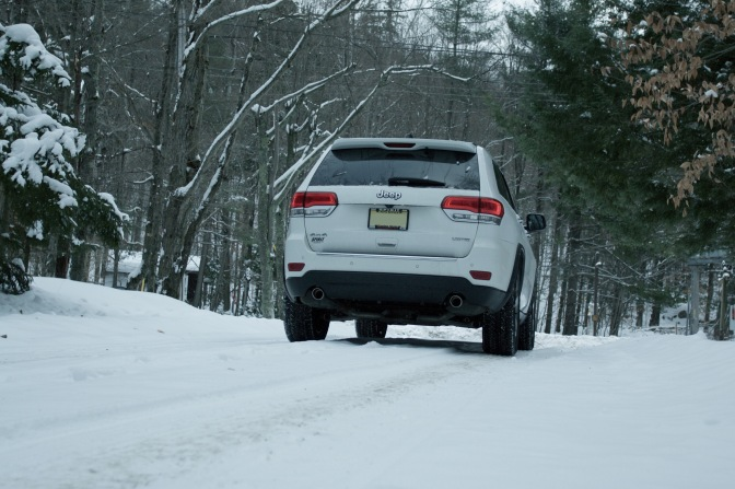 2014 Jeep Grand Cherokee on a snow-covered mountain road.