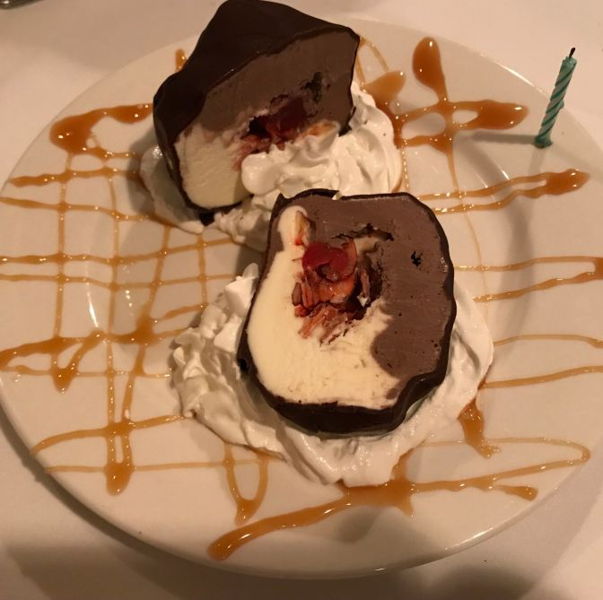 Chocolate and vanilla tartufo, with caramel drizzled across the plate. A candle is attached to the side of the plate.