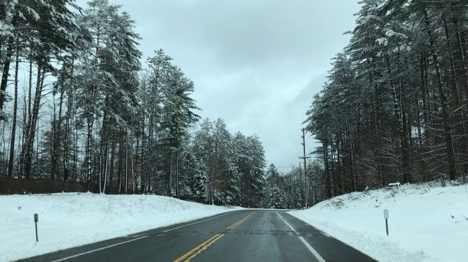 Snowy road in the Adirondacks, with snow covering the trees.