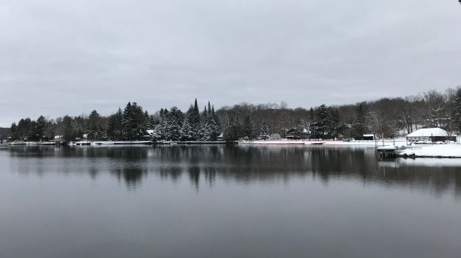 Snow-covered coastline alongside a lake.
